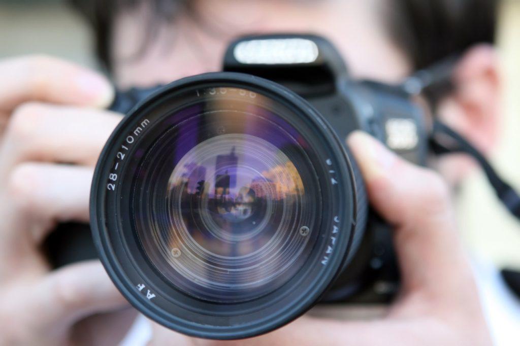 カメラのレンズを正面に向ける男性