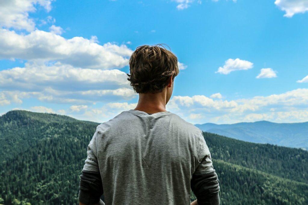 高いところから山を眺める男性