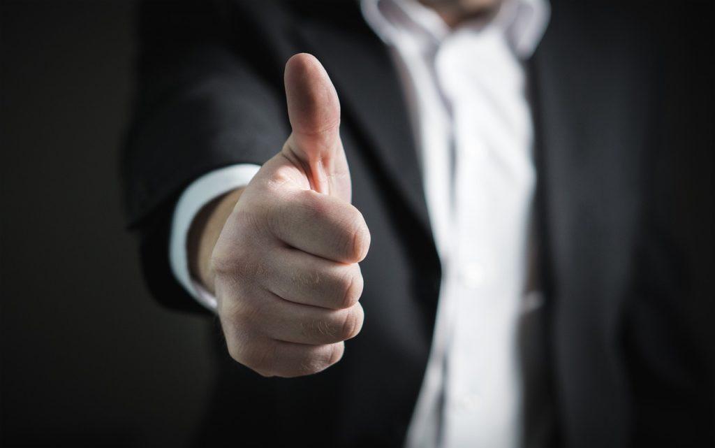 親指を立ててGoodのポーズをしているビジネスマン