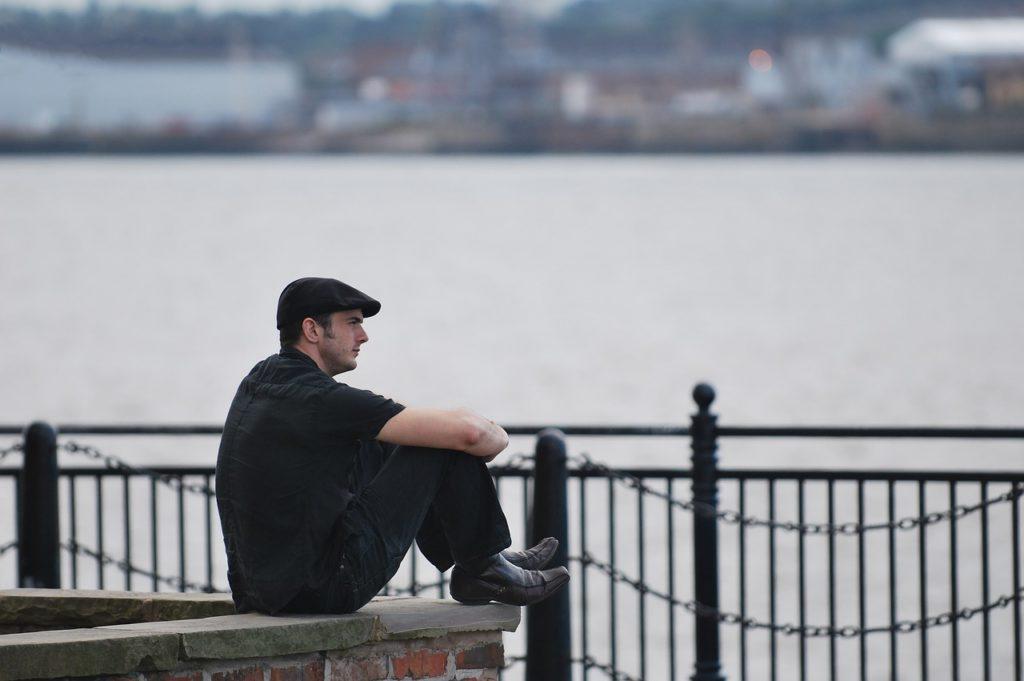 海辺で膝を抱えて考え込む男性