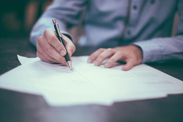 ペンで紙に文字を書く人