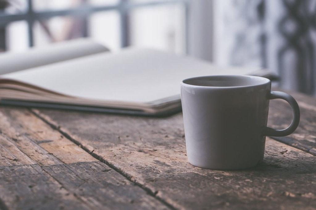 デスクの上にあるコーヒーと本